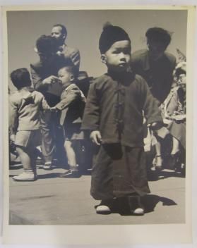 Asian Boy Stands in Front of Crowd in Traditional Garb