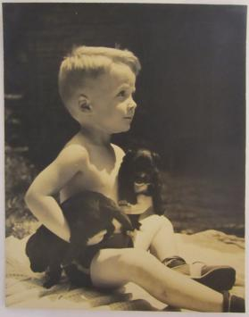Blonde Boy Sits and Plays with Two Puppies