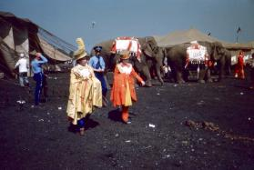 2 ladies in red and yellow garb in front of elephants in BY